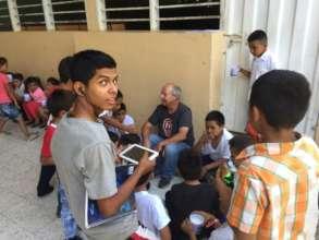 Volunteer, Paul C, sitting with students