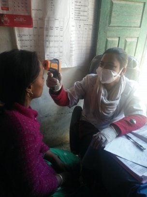 COVID-19 - Dr Meena takes a patient's temperature