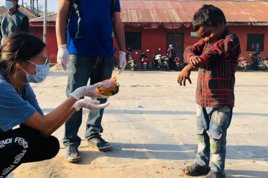 Yuna hands out food in the streets of Kathmandu
