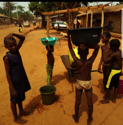 More community residents accessing water source.