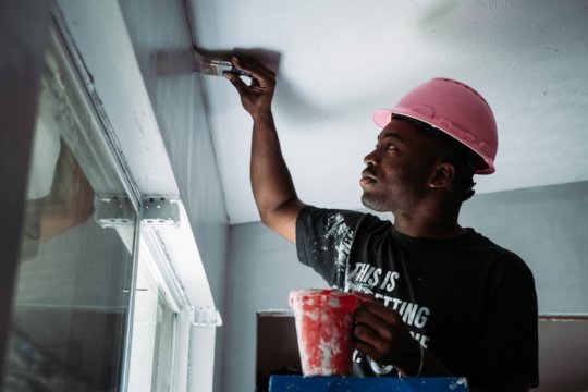 A volunteer applies touch-up paint to the ceiling