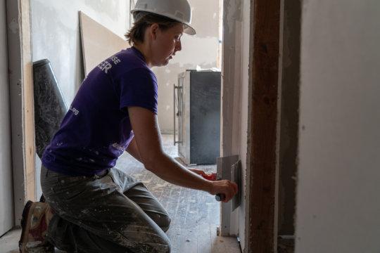 Site Supervisor Emily mudding a corner of a room