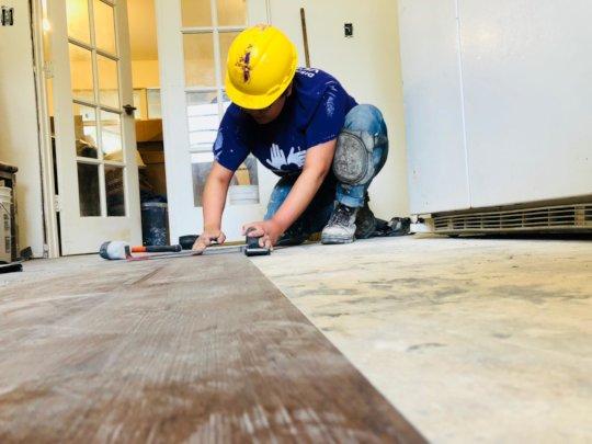 A volunteer lays waterproof flooring at a home