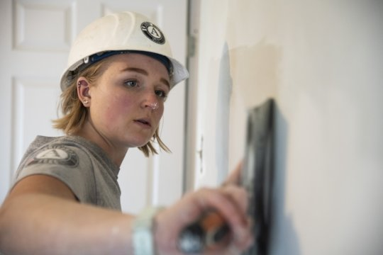 An AmeriCorps member repairs drywall for a home