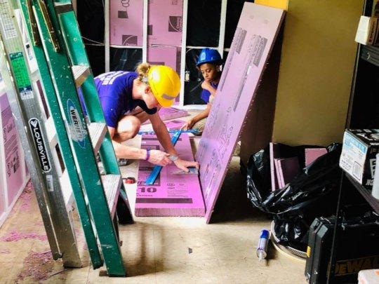 A site supervisor cuts styrofoam insulation