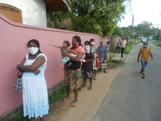 Queuing families waiting for food parcels