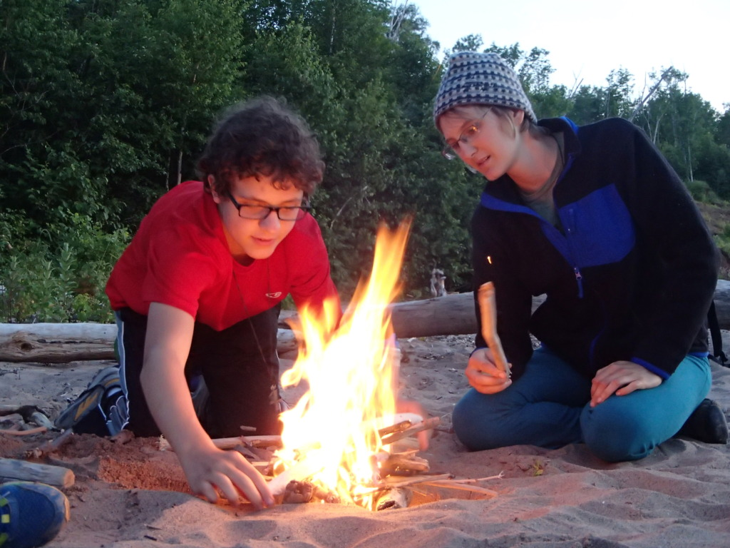 Learning how to build a fire with a staff member.
