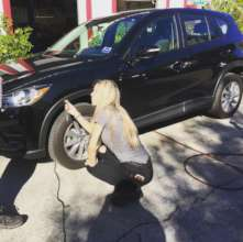 A volunteer learning to check tire pressure