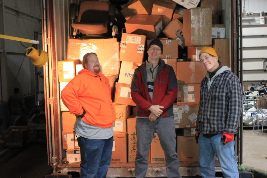 Mike, Dave, and Joel finish loading a container.