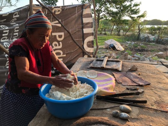 Woman making totopos in a destroyed kitchen