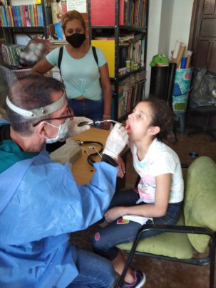 Medical team examines orphan girl's tonsils.