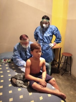 Doctor gives medical exam to young orphan boy.