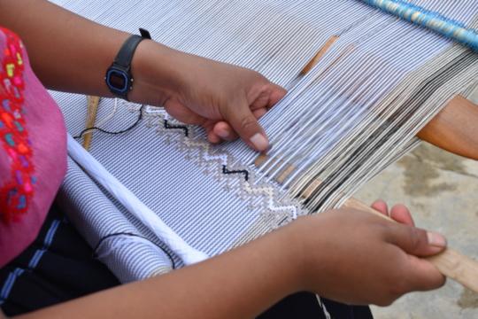Maria weaves on backstrap loom for Ensamble Artesa