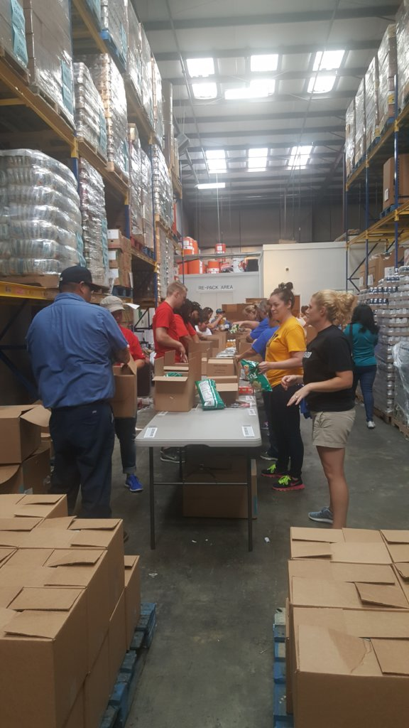 Volunteer group assembling 3,000 family food boxes