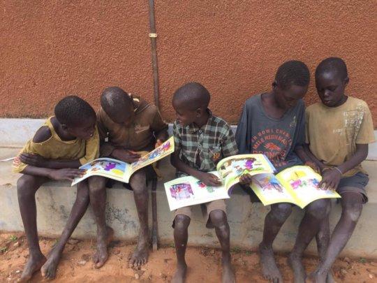 Random children found on the street sit to read