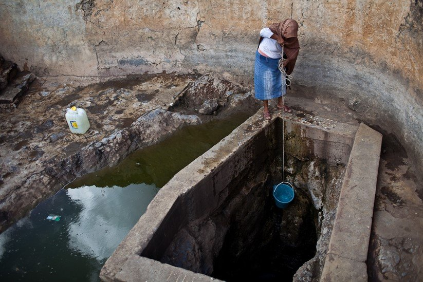 Midwife VIctoria draws water at the well.