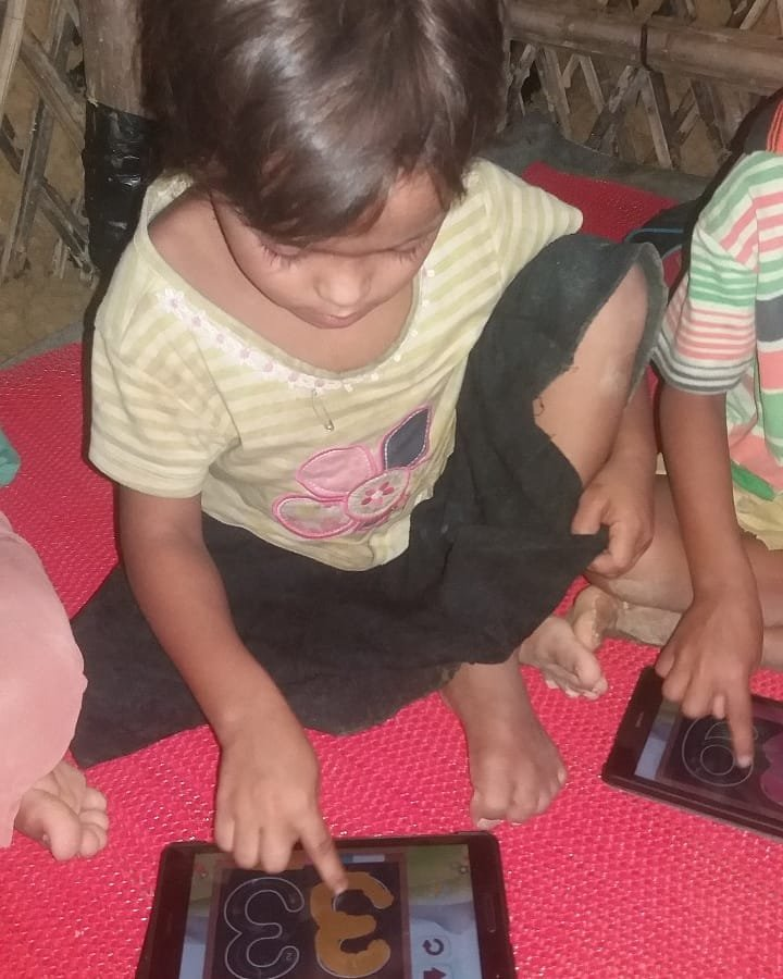 A child learns to read on a tablet