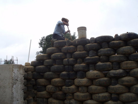 A member of the crew packs the tires with earth.