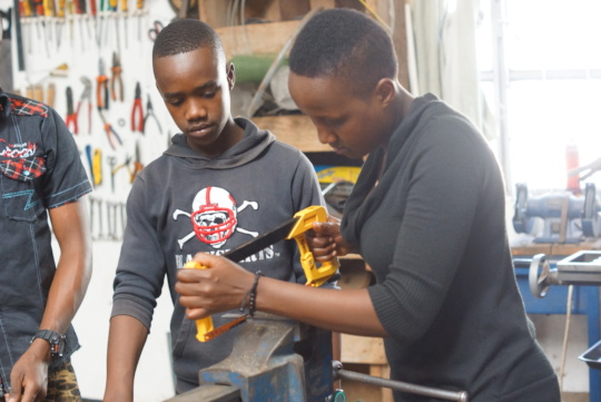 Bahati sawing metal for her bottle opener