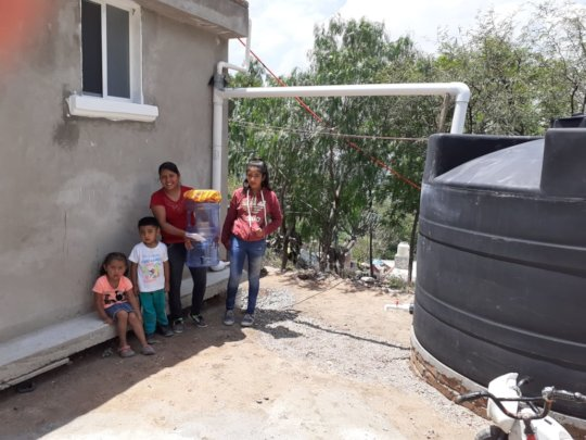 A family shows off their new rainwater system