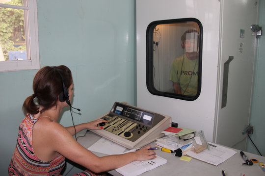 Kathy being tested in the sound-proof booth