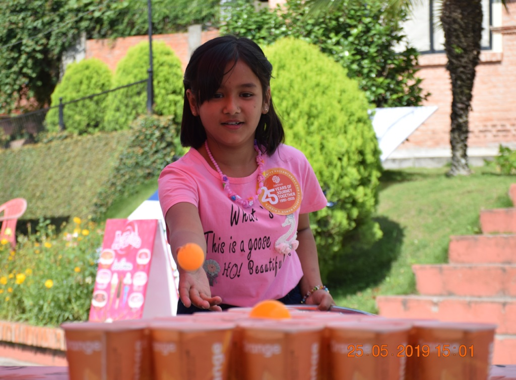 A girl trying to score the cups.