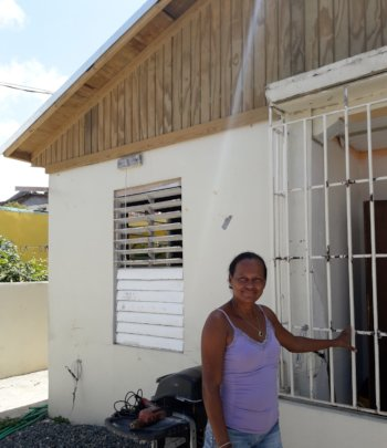 Brenda in Front of Her Newly Roofed Home