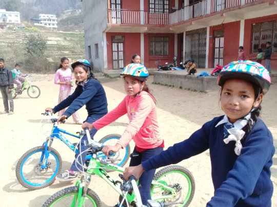 Girls learn to ride new bikes for their school run