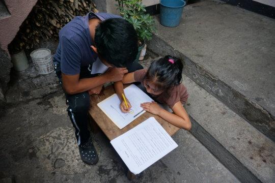 Israel helping Damaris with her work