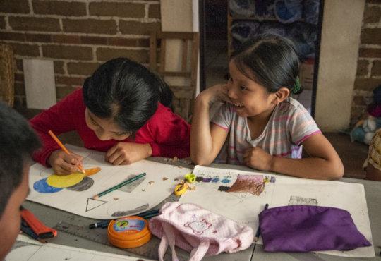Hadasa draws next to her giggling sister Damaris