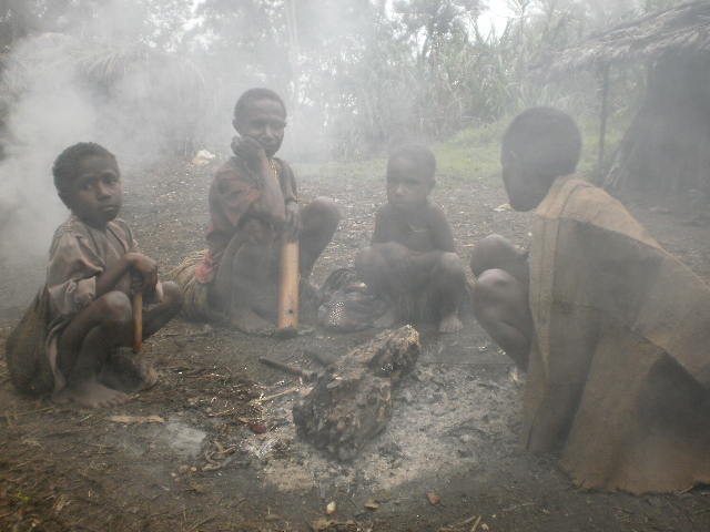 Children inhaling smoke from an open fire