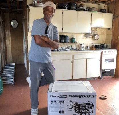 Resident happily poses with his new generator.