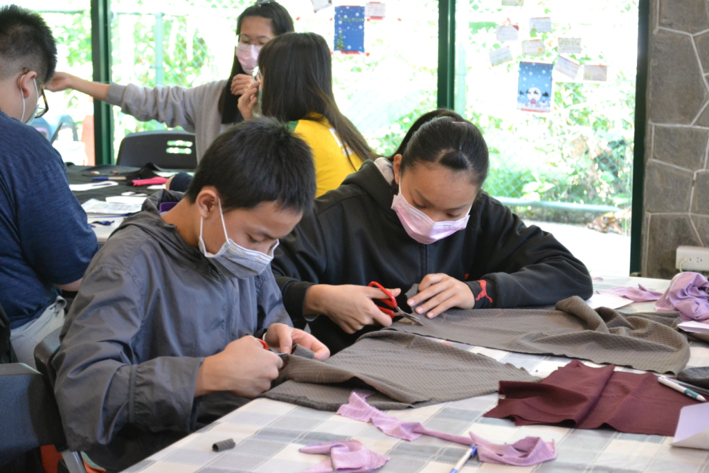 Children are cutting cloth for handmade masks.