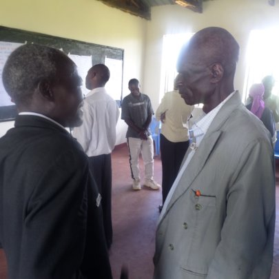 Village Elder Micheal sharing in a group of two's.
