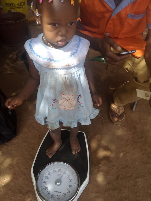 CHW weighing a child