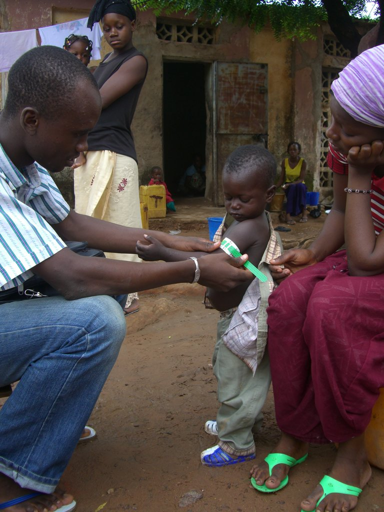 A community health worker measures a child