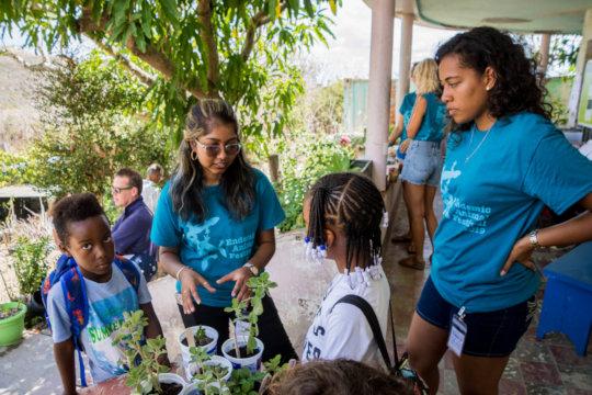 Student volunteers teach kids about plants.