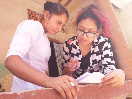 Dikshya with a young woman filling out a survey