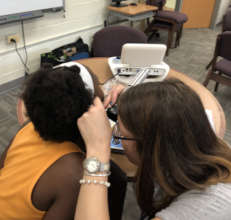A CC audiologist examines the inner ear of a child