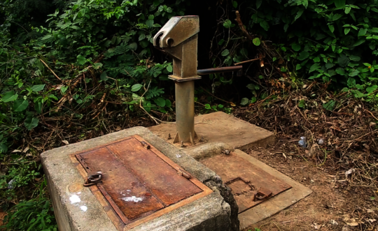 The broken hand pump which lies rusted and idle.