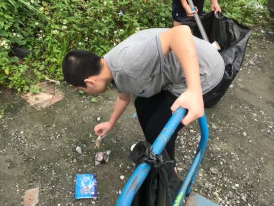 A Boy bend down to pick up trash