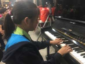 A little girl in children's home playing piano