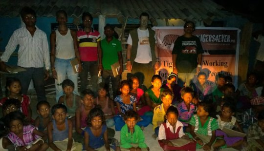 Education packs distributed in a village at night
