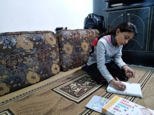 Maram, 12, studies at her home in Syria.