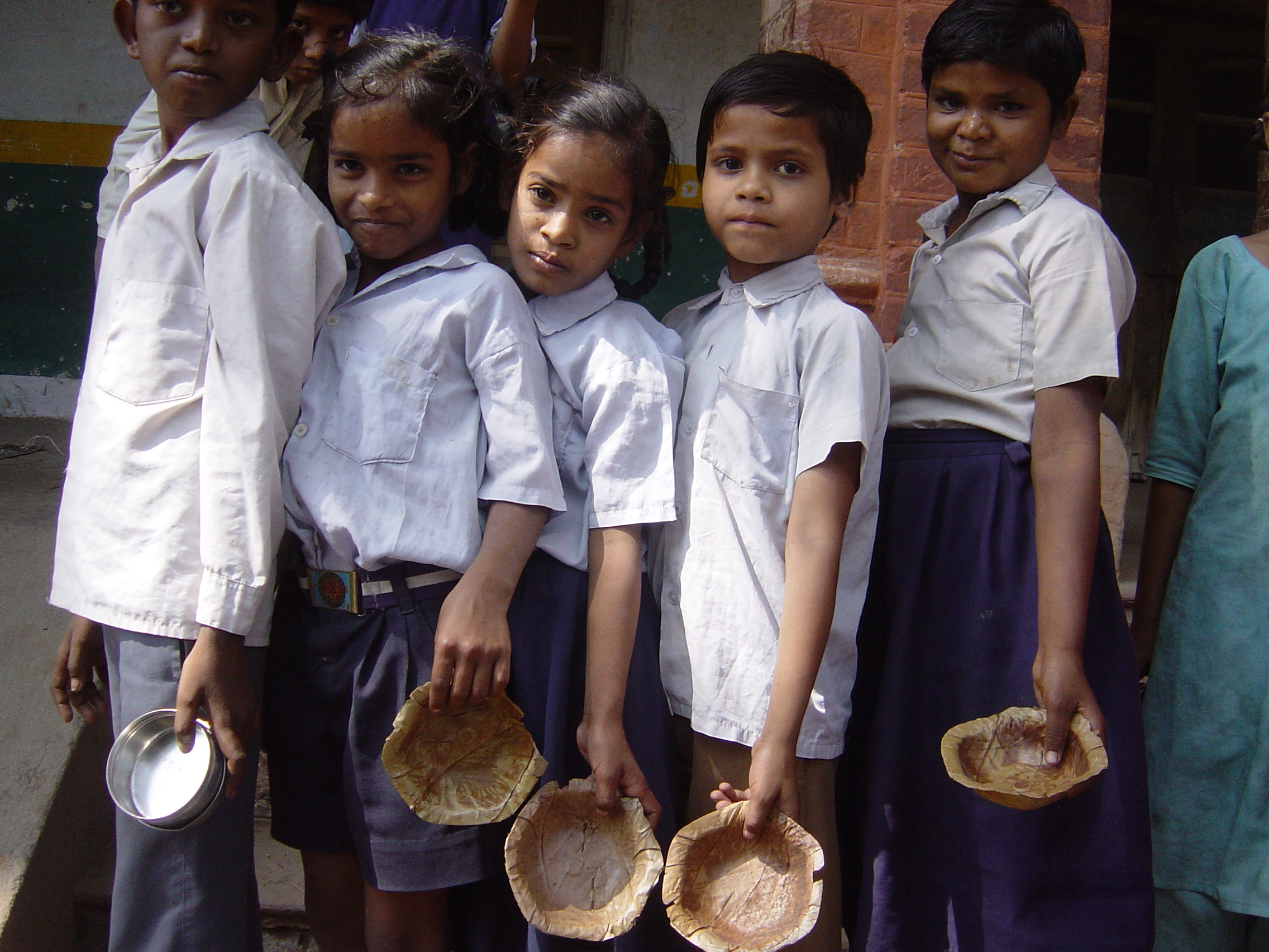 Akshaya Patra beneficiaries wait in line with their bowls to receive what might be their only meal of the day served at school. This meal encourages them to attend school instead of taking up menial jobs.