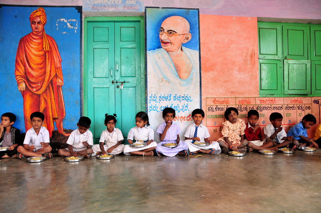 Children eating lunch - AC Nielson, an independant research firm found that the Akshaya Patra meal program increase school enrollment, attendance, and retention especially in girls. Children also experience improved performance and health