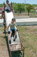 "Children of Otates, Mexico ""play"" on rusted slide"