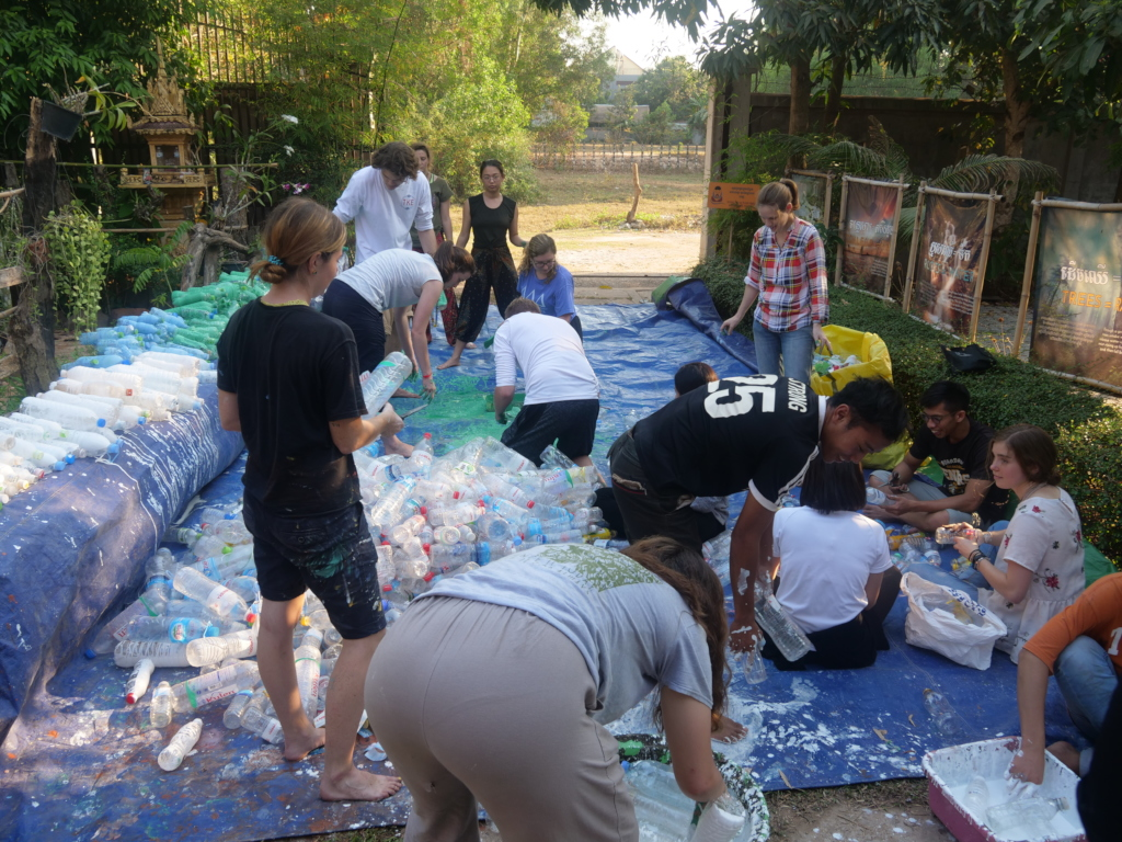 Students paint bottles for the plastic project