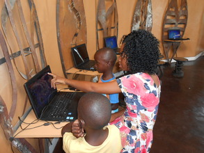Pauline teaching computer games to two little ones