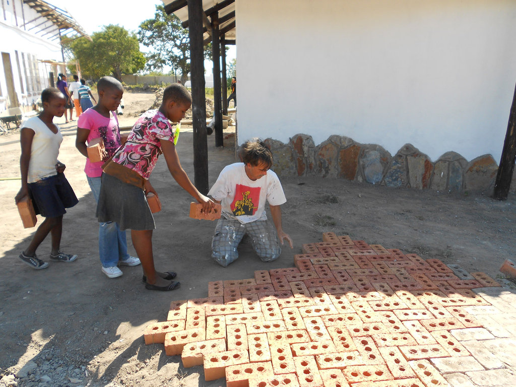 Kids bringing bricks help build our path